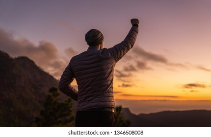 young man standing on mountain top with his arm rised to the sky