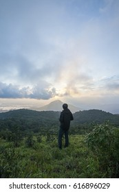 young man standing on the mountain. looking the sunset.Thailand.