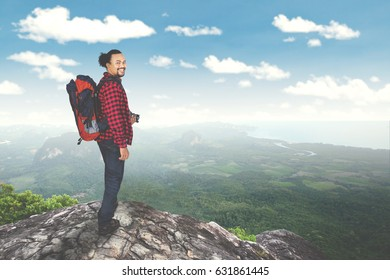 Young man standing on the mountain and smiling at the camera while carrying a backpack for hiking