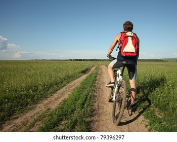 Young man standing on road with bicycle