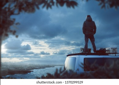 Young man standing on the roof of a camper van enjoying the view of a beautiful coastline at twilight