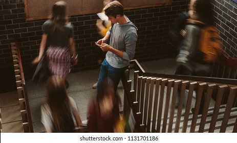 Young man standing on the staircase in college with girls walking by. Students on steps of college campus.