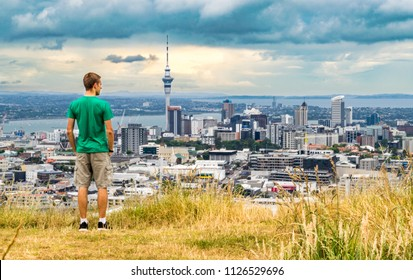 Young man standing on the summit of Mt. Eden overlooking the Auckland skyline at sunset - Auckland, New Zealand (city center/ downtown)