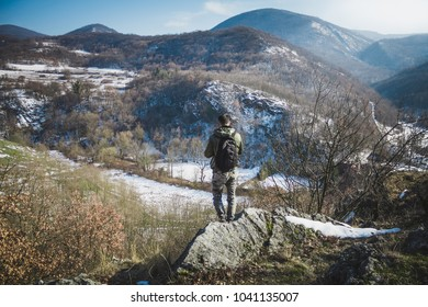 Young man standing on top of cliff in winter mountains holding a camera and enjoying view. Hiker with backpack standing on a cliffs edge on the top of mountain with gorgeous view to forests and valley
