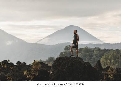 Der junge Mann steht auf Stein und genießt den fantastischen Ausblick auf den Vulkan Agung in Bali. Reisen und aktives Lifestyle-Konzept.