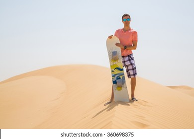 Young man standing on the top of the dune with a sandboard in the middle of the Atacama desert