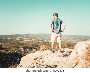 Young Man Standing on top of a Cliff, looking across a valley