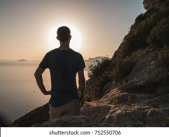 Young Man Standing on top of a Cliff, looking at the ocean