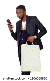 young man standing on white background in jacket looking at mobile phone while smiling.