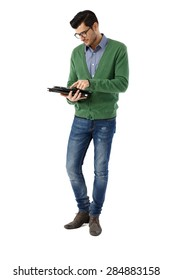 Young man standing over white background, holding and using tablet pc. Full-length.