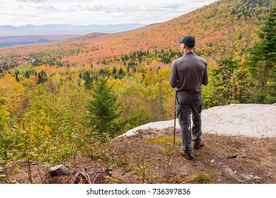 Young man standing at panoramic lookout on Megantic Mount in Canada, enjoying autumn colours