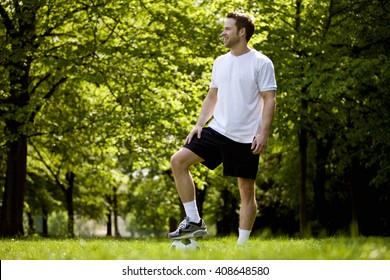A young man standing in the park with his foot on a football