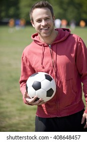 A young man standing in the park, holding a football