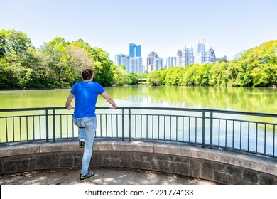 Young man standing in Piedmont Park in Atlanta, Georgia looking at scenic view, water, cityscape, skyline of urban city skyscrapers downtown, Lake Clara Meer
