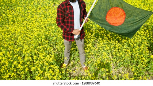 Young man standing in a place holding the Bangladeshi national flag