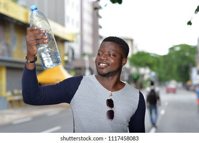young man standing in polo on the street looking at bottle of water in hand laughing.