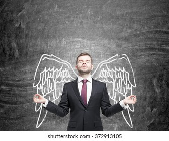young man standing in a posture of meditation in front of a blackboard with angel wings painted on it as if they were his. Front view. Concept of lending wings.