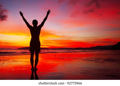 Young man standing with raised hands on a beach