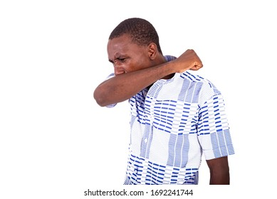 young man standing in shirt coughs in his elbow.