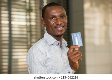 young man standing in shirt shows credit card, looks at camera smiling.