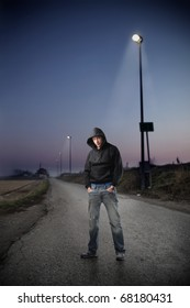 A young man standing in a street by night