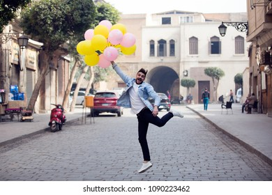 Young man standing in the street holding balloons raising his leg like he will fly and the balloons raising him up.