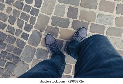 Young man standing in at the street in a oldtown in casually dressed sneakers, Point of view shot