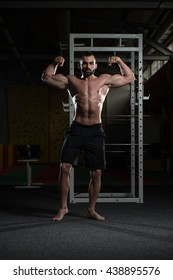 Young Man Standing Strong In The Gym And Flexing Front Double Biceps Pose - Muscular Athletic Bodybuilder Fitness Model Posing Exercises
