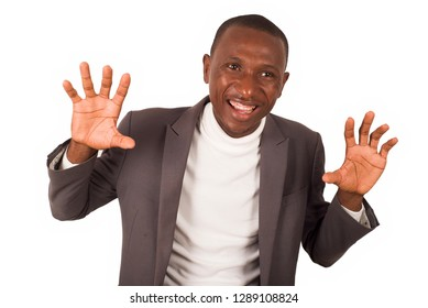young man standing in a suit on a white background smiling at the camera while doing gestures.