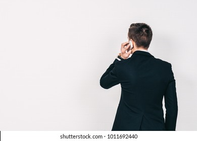 Young man standing and talking on the phone over a white background, back view, copy space