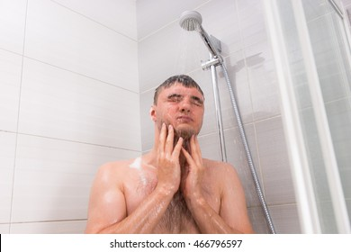 Young man standing under flowing water in shower cabin with transparent glass doors in the modern tiled bathroom