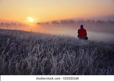 Young man standing in winter frozen nature and watching to the calm winter misty sunrise. Original wallpaper or background from nature - thinking concept, photo full of freedom, beautiful landscape
