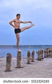 Young Man Standing Yoga Pose On Wooden Pillars.