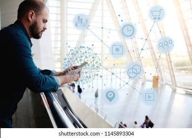 Young man stands in airport interior and checking online schedule of flights through mobile phone application. Hipster guy surfing network, connecting with people and shopping. Infographics symbols