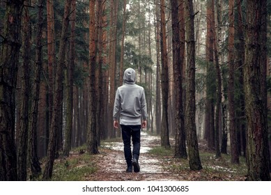 A young man stands back in the forest.