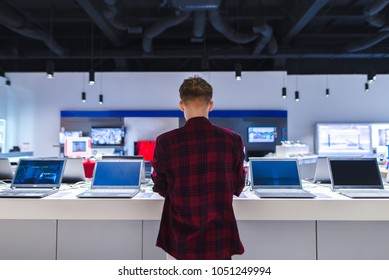 A young man stands behind his laptop at the electronics store. A young man chooses a laptop in the store