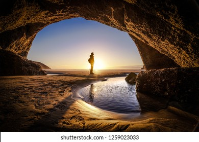 Young man stands at a cave exit. A person deep thinking at the exit of a cave. Beautiful landscape formation of a cave in New Zealand