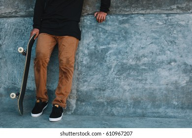 Young man stands in a concrete skate park with his skateboard in black sneakers