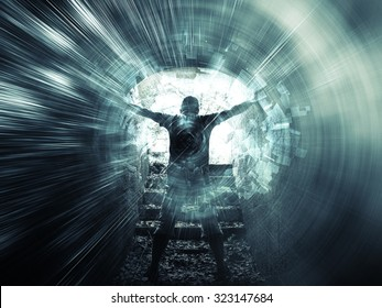 Young man stands in dark blue tunnel with glowing end and abstract lights structures