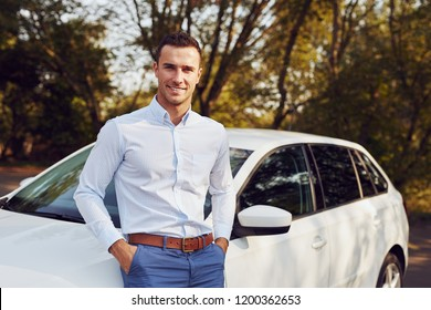 A young man stands in front of his new car