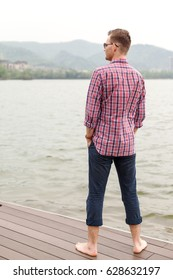 A young man stands near a lake. A young man is traveling.