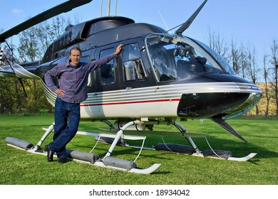 Young man stands next to small private helicopter on grass in estate. Shot  near Cape Town, Western Cape, South Africa.