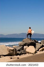 A young man stands on the coastline and looks at the surf condition.