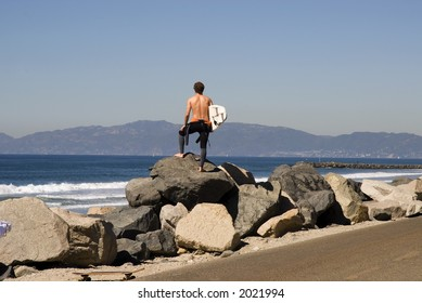 A young man stands on the coastline and checks surf conditions