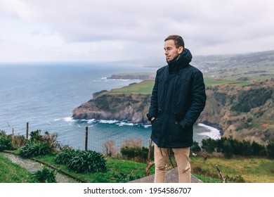 A young man stands on the edge of a cliff against the backdrop of a lake and looks into the distance. The concept of travel to beautiful nature.