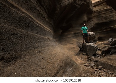 Young man stands on rock on scenic sandstone canyon in Gran Canaria, Spain. Hipster with adventure spirit looking up on brown smooth wall passageway corridor in Canary Islands