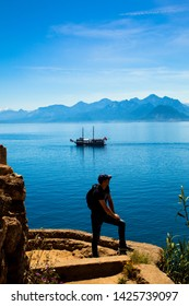 Young man stands on a rock on the background of a beautiful view of the Mediterranean Sea, the mountains and the ship. Turkey, Antalya.