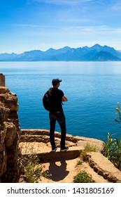 Young man stands on a rock on the background of a beautiful view of the Mediterranean Sea and mountains. Turkey, Antalya.