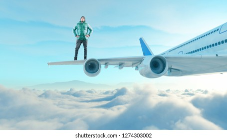 The young man stands on the wing of a plane above the clouds.