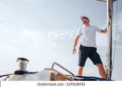 Young man stands on yacht board and looks forward. He holds on mast with hand. Young man poses. He wears white shirt and black shorts.